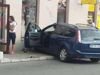 FOTO - Accident în centrul municipiului Sighet: Un autoturism a rupt un stâlp și s-a oprit în geamul unui magazin după ce un altul nu a oprit la STOP