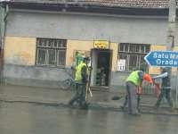 MADE ÎN SIGHET - Deși ploua cu găleata, muncitorii turnau asfalt prin tranșeele rămase în urma lucrărilor de apă-canal